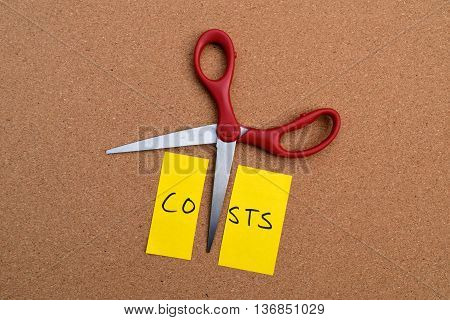 cutting costs represented with scissors and a sticky note
