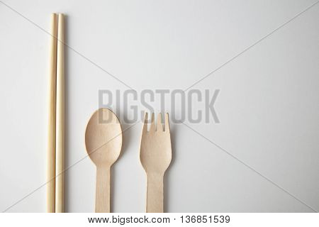 Mixed of kitchen utencils for takeaway: asian chopsticks, spoon or fork made from recycled paper or wood, eco friendly, top view isolated on white
