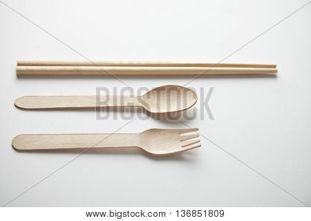 Mixed of kitchen utencils for takeaway: asian chopsticks, spoon or fork made from recycled paper or wood, eco friendly, top view presented top view on white