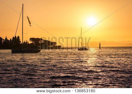 Silhouette of sailboats in sunset, summer time in touristic city Supetar, Island of brac, Croatia.