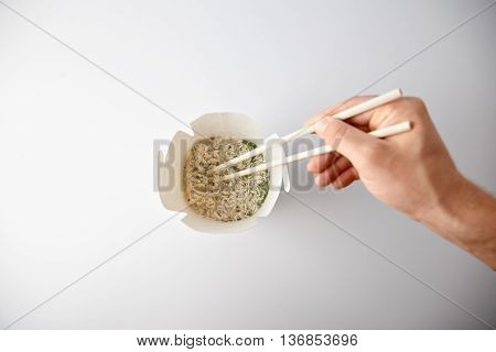 Top view, hand with chopsticks twist freshly cooked wok noodles soup inside blank takeaway box isolated on white Commercial promo
