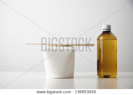 Retail takeaway presentation business set: plastic transparent brown bottle with drink near closed blank paper box with wok noodles inside and chopsticks on top isolated on white