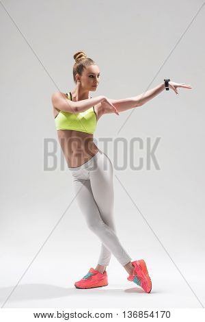 Beautiful female dancer is training in sportswear. She is standing and stretching her arms sideways. The woman is looking aside with aspiration. Isolated