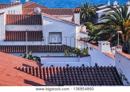 Chalets with roofs from terracotta tiles beside Mediterranean Sea. Top view. Summer vacations concept. Horizontal.