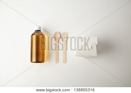 Commercial retail takeaway promo, top view simple set, plastic brown bottle with drink, closed blank noodles box and recycled eco friendly spoon and fork presented isolated on white top view