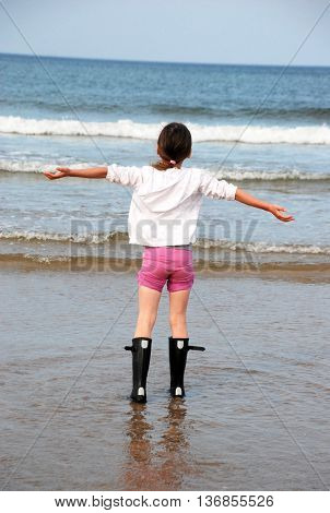little girl feels joy and happiness near the sea waves after the rain enjoying open arms