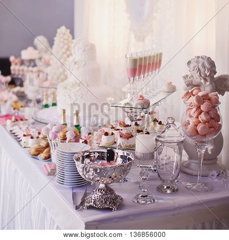 Dessert table for a party. Ombre cake cupcakes sweetness and flowers