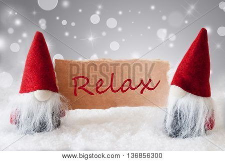 Christmas Greeting Card With Two Red Gnomes. Sparkling Bokeh And Noble Silver Background With Snow. English Text Relax