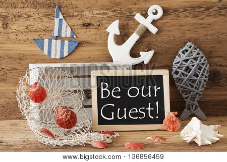 Blackboard With Nautical Summer Decoration And Wooden Background. English Text Be Our Guest. Fish, Anchor, Shells And Fishnet For Maritime Contex.