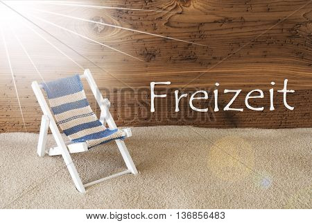 Sunny Summer Greeting Card With Sand And Aged Wooden Background. German Text Freizeit Means Leisure Time. Deck Chair For Holiday Or Vacation Feeling.