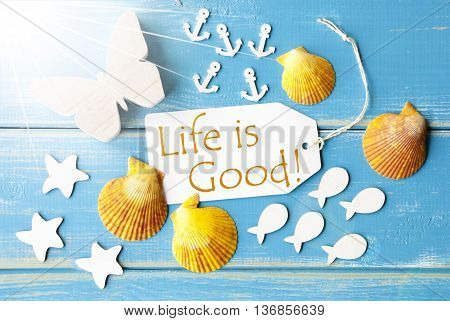 Flat Lay View Of Label With English Text Life Is Good. Sunny Summer Greeting Card. Butterfly, Shells And Fishes On Blue Wooden Background