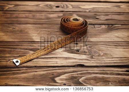 Vintage tailor ruler rolled isolated on rustic wooden table close up