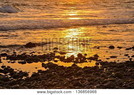 Gravel beach in amber sunlight. Costa Dorada, Spain.  Horizontal.