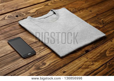 Blank grey t-shirt accurately folded near black smartphone gadget on rustic wooden table side view