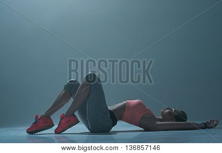 Pretty fit dancer is lying on flooring and posing. She is looking up confidently