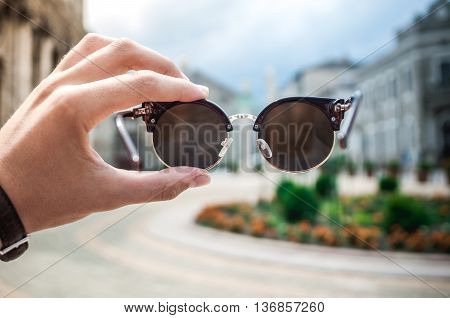 Sunglasses in hand on blurred background. Cool sunglasses
