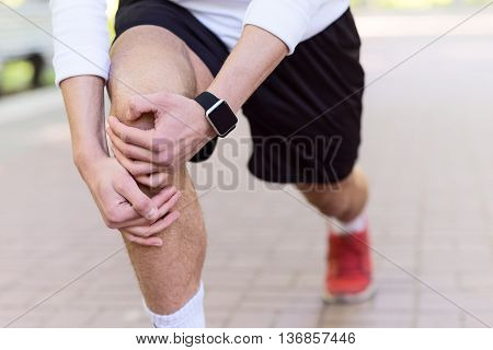 Close up of young man stretching his leg before running. Man has tracker on wrist
