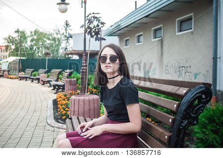Beautiful girl in a red skirt, sitting on a bench in the town center and waiting friends. She straightens hair