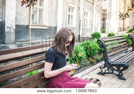 A young girl with beautiful hair and a black T-shirt, waiting for friends. She straightens hair at school and using the phone. Pretty Girl. Wind develops hair