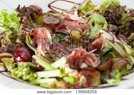 Bowl of salad with lettuce and grapes and parma ham
