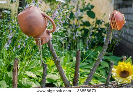 Ancient traditional Ukrainian clay pot standing on a cut tree in summer garden