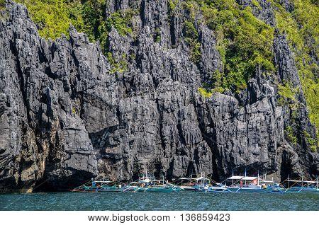 Bancas in front of huge rocks miniloc island. El Nido, Palawan, Philippines