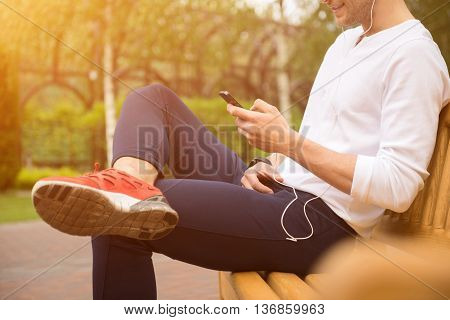 Joyful young man is relaxing in park. He is using mobile phone while listening to music from headphones. Sportsman is sitting on bench and smiling