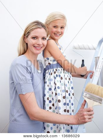 Happy mother and her daughter painting a wall in new house