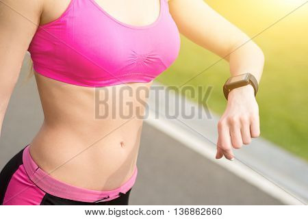 Close up of young sporty woman looking at tracker on her arm. She is standing outdoors