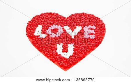 Red WHite and Pink candy hearts for Valentine's day arrainged in a large heart on a white background whit the phrase love u visible.