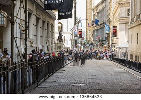 New York, USA - June 18, 2016: Fenced off New York Stock Exchange with people walking on Wall Street