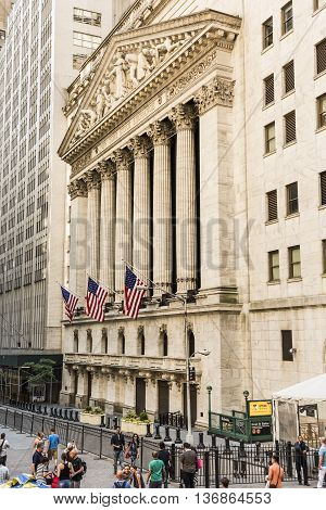 New York, USA - June 18, 2016: Vertical view of the New York Stock Exchange with American flags and people walking