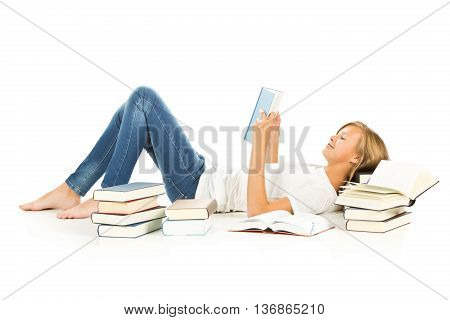 Young girl lying on the floor with books reading over white background