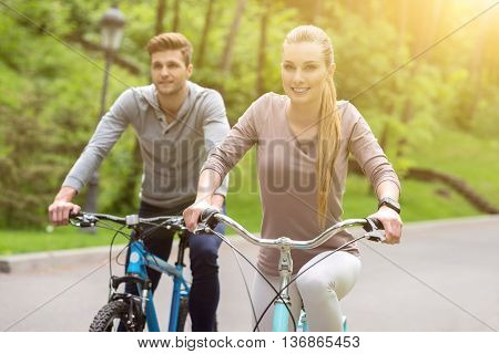Loving couple are making trip by bicycles. They are looking forward with happiness and laughing