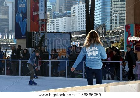 Sydney Australia - July 3 2016. Girl skating on the ice rink in Darling Harbour. The Winter Festival's in Sydney are Australia's largest winter events featuring open-air ice-skating.