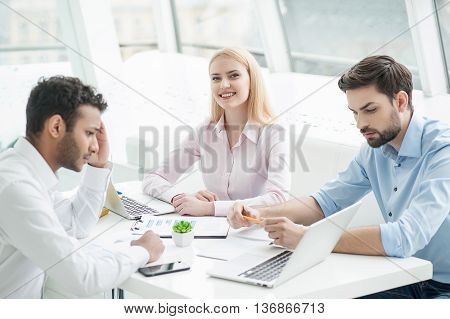 Brainstorming project. Group of young business people discussing something while sitting together and looking at paper laying on desk