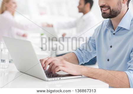 I have ot of ideas. Close up of businessman working in modern office, using laptop with partners in background