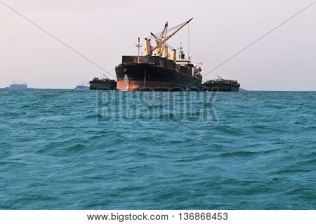 Cargo ship with small boat beside waiting to transfer things