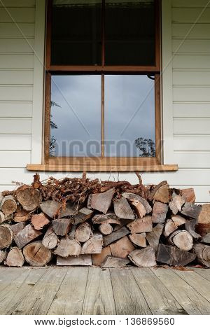 Firewood logpile stacked under a window on a wooden verandah of a weatherboard home. Portrait orientation. Photographed in New Zealand.