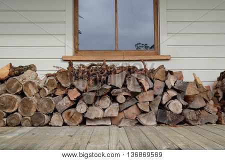 Firewood log pile stacked under a window on a wooden veranda of a weatherboard home. Landscape orientation. Photographed in New Zealand.