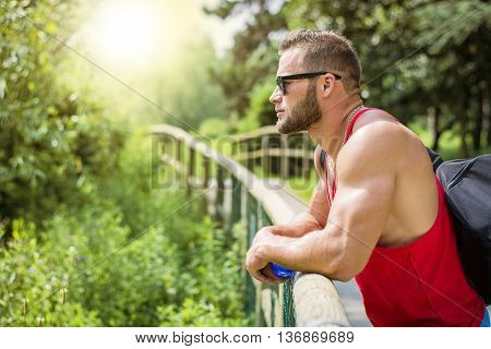 Handsome Muscular Hunk Man Outdoor in City Park, During Daytime, Wearing Tanktop and Sunglasses