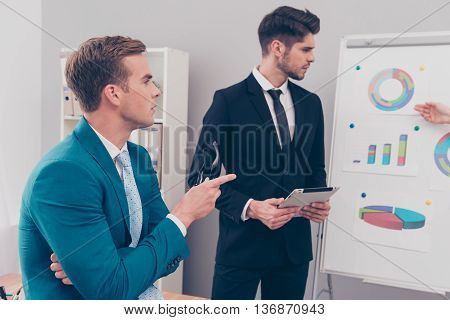 Two Young Businessmen Discussing Diagrama Of  Financial Growth Of Their Company