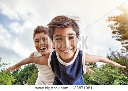 Happy brothers having fun outdoors, playing as if flying, two active boys spending summer holidays w