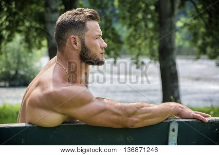 Handsome Muscular Shirtless Hunk Man Outdoor in City Park. Showing Healthy Muscle Body While Looking away, Sitting on Bench