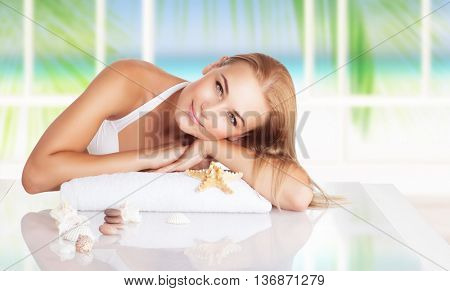 Portrait of a beautiful blond woman relaxing on the beach spa resort, lying down on massage table decorated with seashells, enjoying peaceful summer vacation