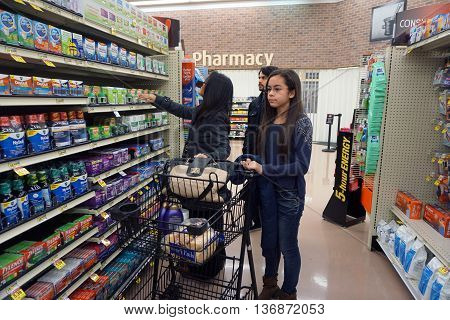 JOLIET, ILLINOIS / UNITED STATES - NOVEMBER 26, 2015: A woman shops for allergy medicine in the pharmacy section of the Jewel-Osco supermarket on Thanksgiving Day.