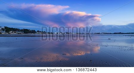 Red skies over a Dorset harbour. Receding stoem clouds are reflected in the wet sand in front of Millionnaires' Row Sandbanks