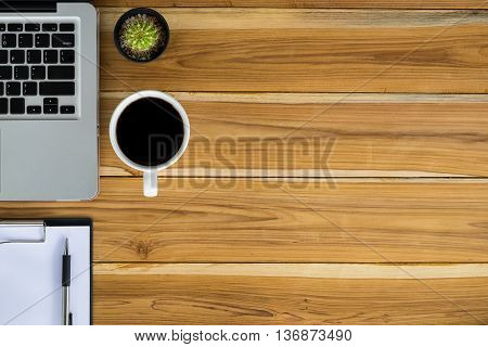 Office workspace with laptop pen empty note paper over blackboard and cup of coffee.top view office gadgets with copy space