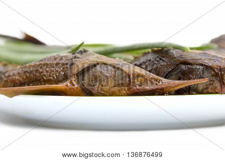 Hot smoked sturgeon on a plate on White background