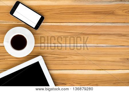 Office stuff with blank screen tablet blank screen smartphone and cup of coffee. Top view with copy space.